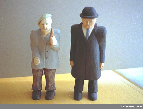 """Till vänster står en gråklädd man med baskern på sned. Han håller en ölflaska i handen. Till höger står en svartklädd man i hatt, slips och vit skjorta. Harry Bergmans """"gubbar"""" (träfigurer)."""