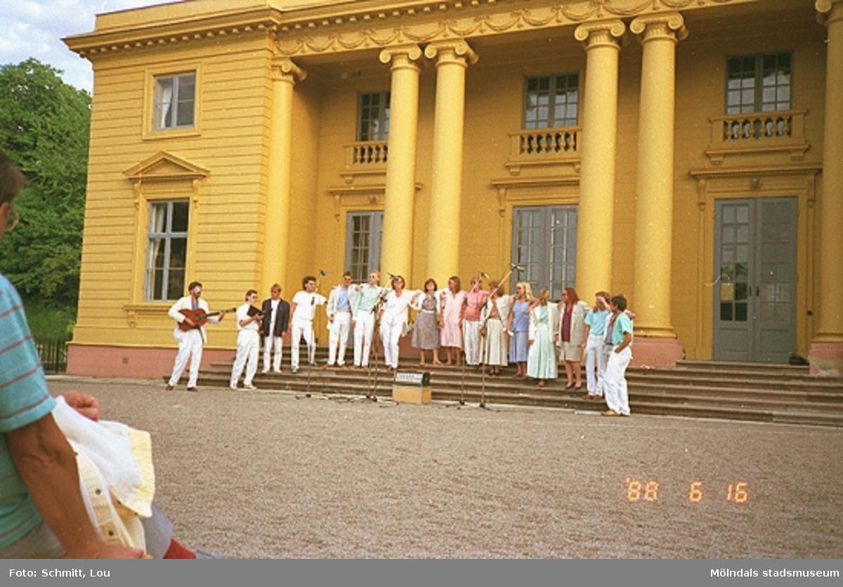 En kör och en gitarrist står uppställda på trappan till Gunnebo slotts framsida. De sjunger och spelar inför publik.
