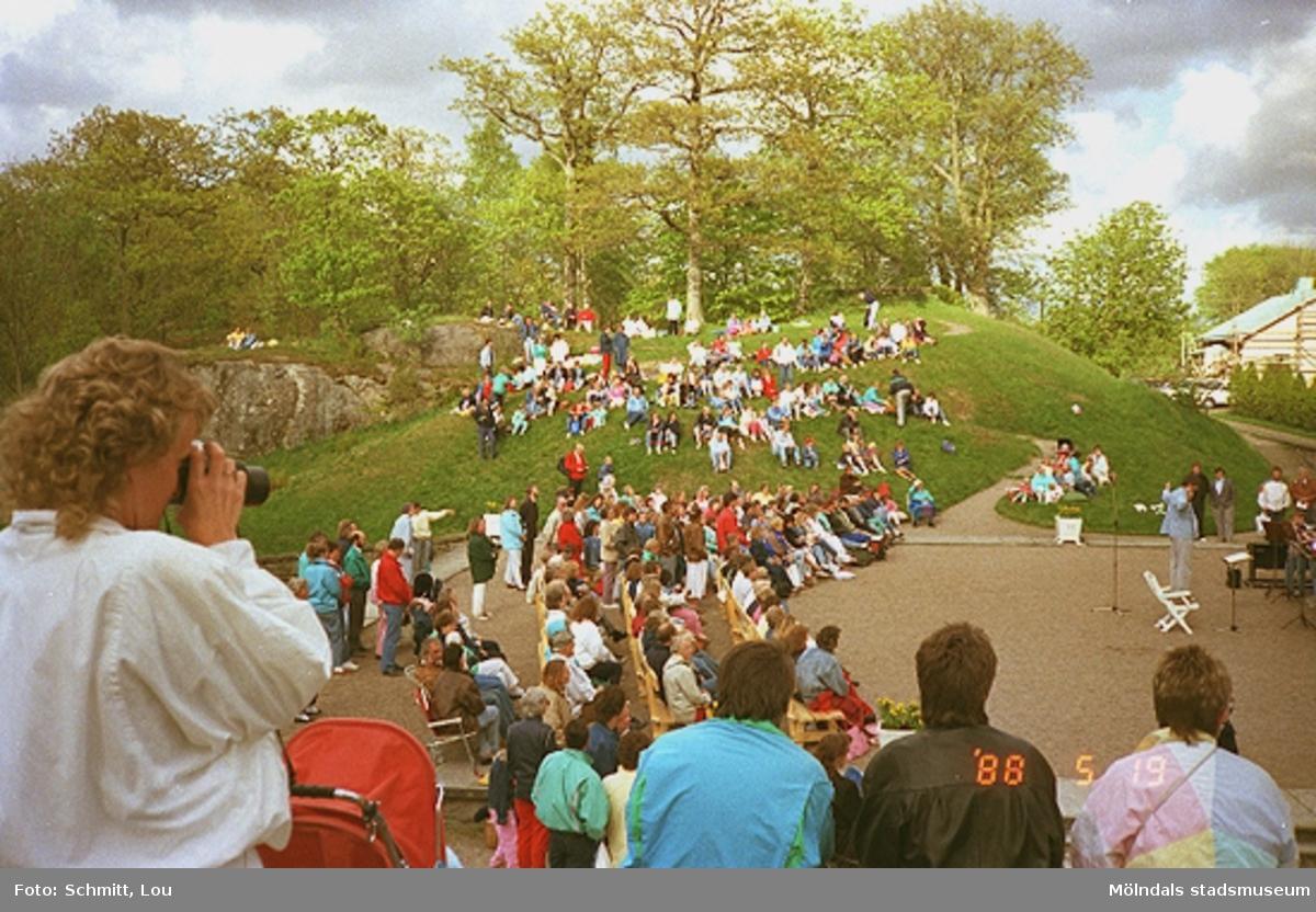 Människor, sittandes på bänkar eller i gräset, som lyssnar på någon sorts musikalisk underhållning som pågår på Gunnebo slotts framsida.