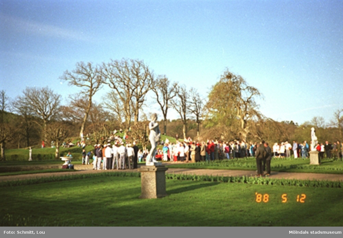 Människor som lyssnar till en studentkör i Gunnebo slottspark. I förgrunden ser man en skulptur ståendes på gräsmattan.