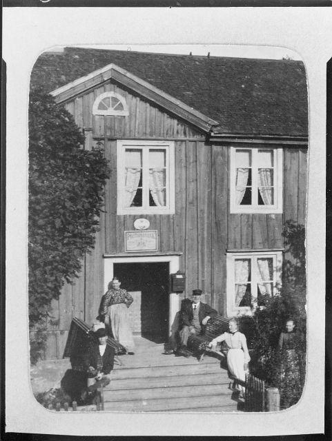 Gamla posthuset i Virserum. Posthuset inrymde en poststation från 1800-talets början till år 1911. Till höger poststationsföreståndare P.A. Nilsson i Virserum med sin familj på posthusets trappa.   Huset revs år 1961, flyttades till Skansen i Stockholm, där det återbyggdes och restaurerades.