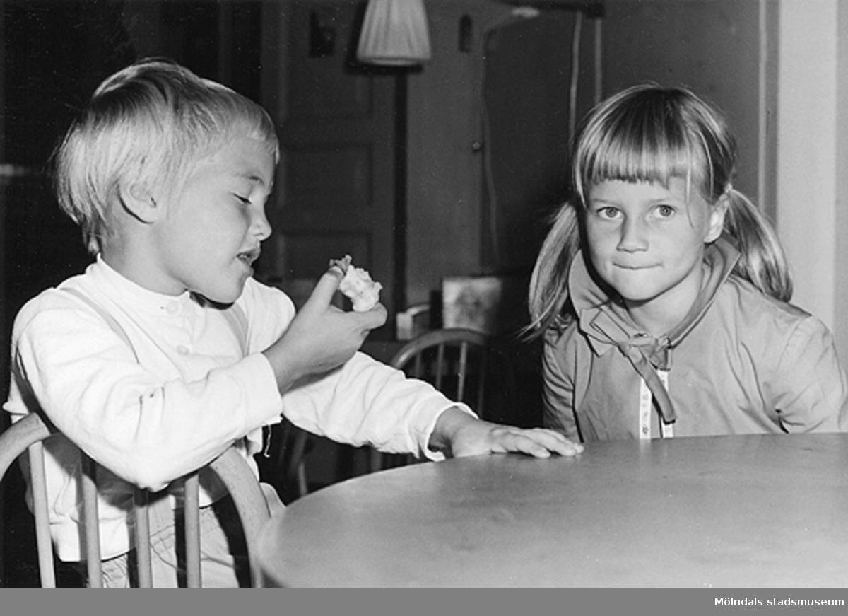 Två barn som sitter vid ett bord. Det vänstra barnet håller en äppleskrott i handen. Holtermanska daghemmet 1953.