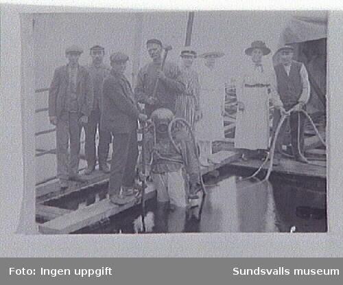 Dykare på väg ned i vattnet. T.v. en luftslang med telekabel och t.h. en signallina i form av ett rep. Omkring denne står medlemmar av familjen Östlin.