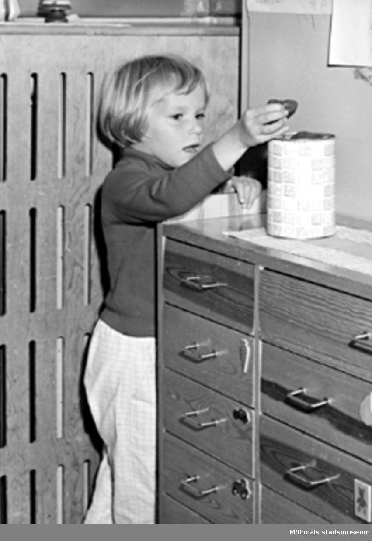 En flicka står vid en skänk och lägger i/tar ur något i en burk. Holtermanska daghemmet 1953.