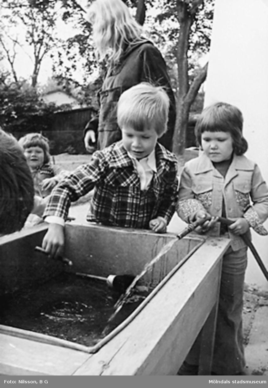Barn som fyller en behållare med vatten. Holtermanska daghemmet juni 1974.