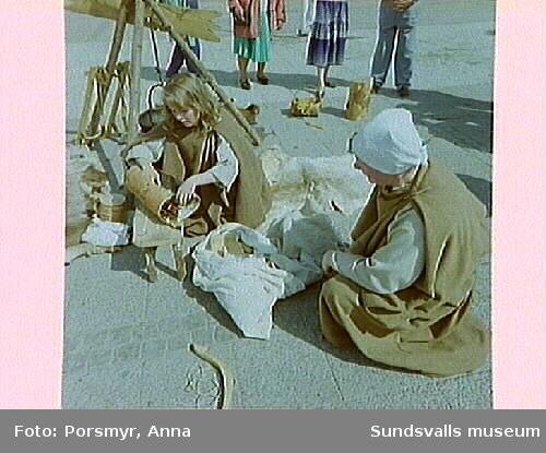 """Gatuteater, """"När Hägvid och Sigsten kommer till stan"""". """"Hövdingen Sigsten och hans hustru Hägvid besöker Sundsvall. De är på väg till hövdingen i Högom för att hämta med sig Tora, Hägvids systerdotter. Tora möter dem på vägen. Sigsten har aldrig sett Tora och tycker att hon ser fasligt klen ut. Hur kommer hon att klara jobbet på gården i Gene? Och hur ska Hägvid någonsin få någon ordning på Sigsten?"""".Sigsten, hövding i Gene framfördes av Torbjörn Thelin, Hägvid, gift med Sigsten och dotter till hövdingen i Högom av Astrid Westin, Tora, Hägvids systerdotter av Annika Björkström.Gatuteatern utgjorde ett smakprov på vad Gene fornby, Örnsköldsvik, har att erbjuda sommarens besökare."""