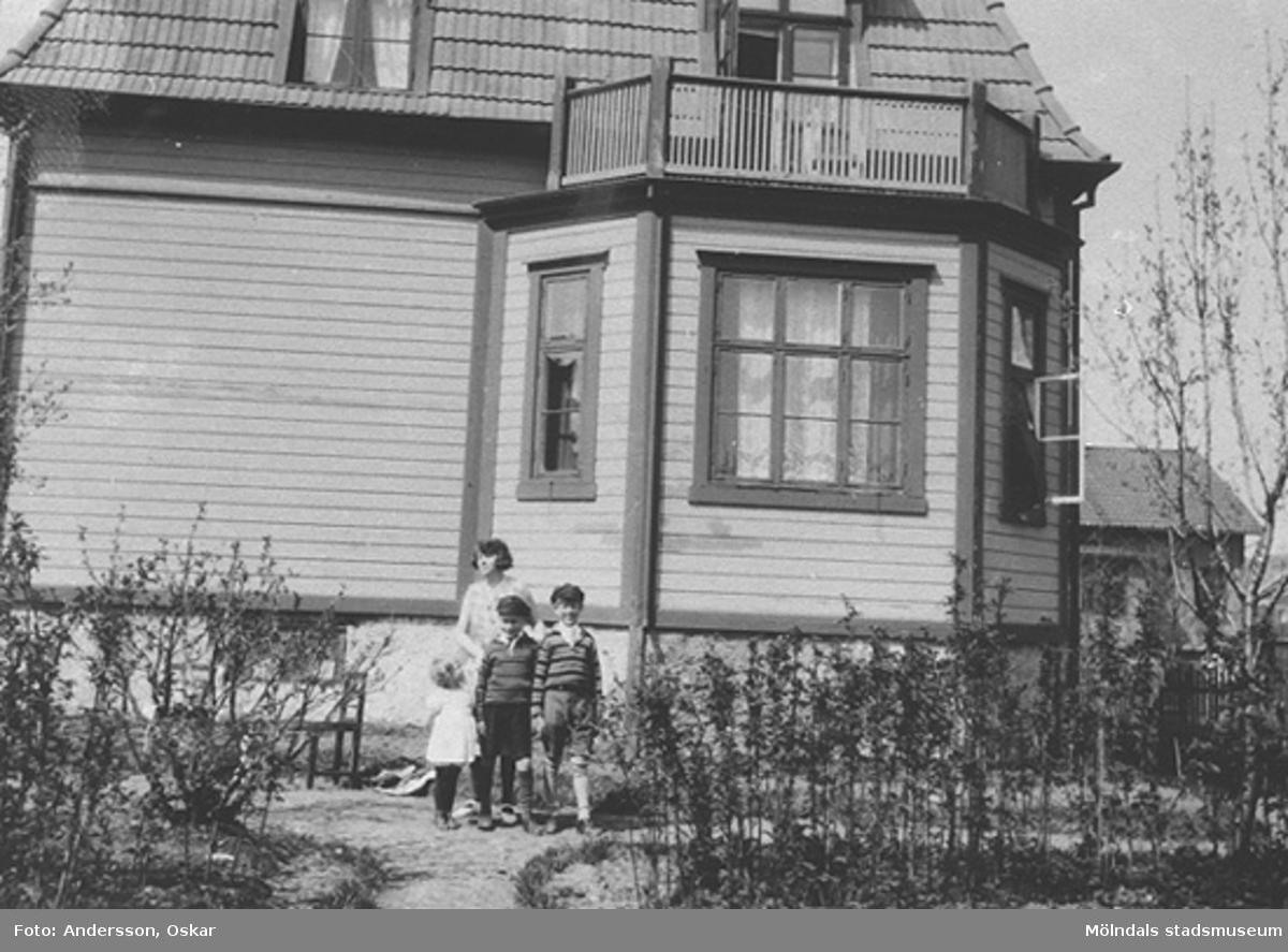 Elisabet Stam Andersson med sina barn Lillemor och Lasse med kompisen Arne, stående framför huset på Barnhemsgatan 13. 1930-talets början.