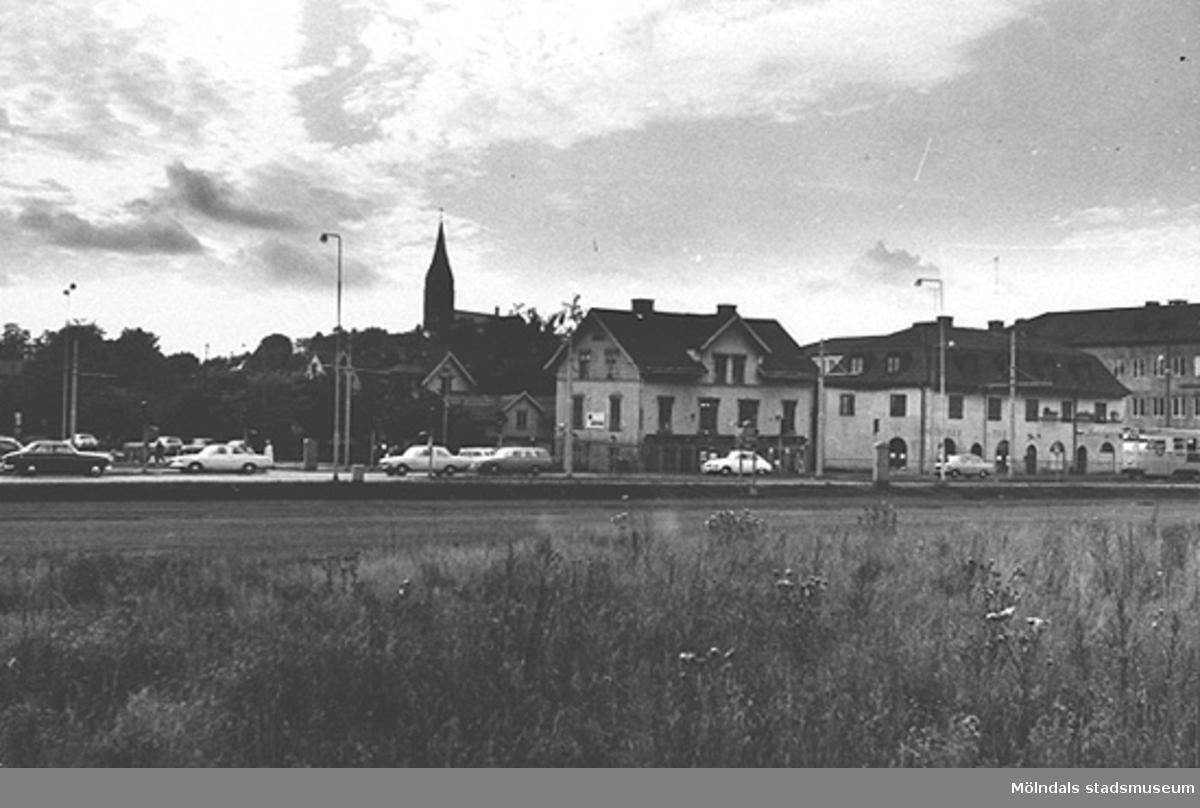 Vy mot affärsbyggnader längs Kungsbackavägen där Fässbergskyrkan syns i bakgrunden, 1970-tal. Man ser Kungsbackavägen 6: Karlssons Järn. Kungsbackavägen 4: Affärsbyggnad, Bergs frisersalong, Skånska bageriet och Landerös radio. Kungsbackavägen 2/Frölundagatan 1: Hantverkshuset, Götabanken,Posten och Restaurang Gillet.