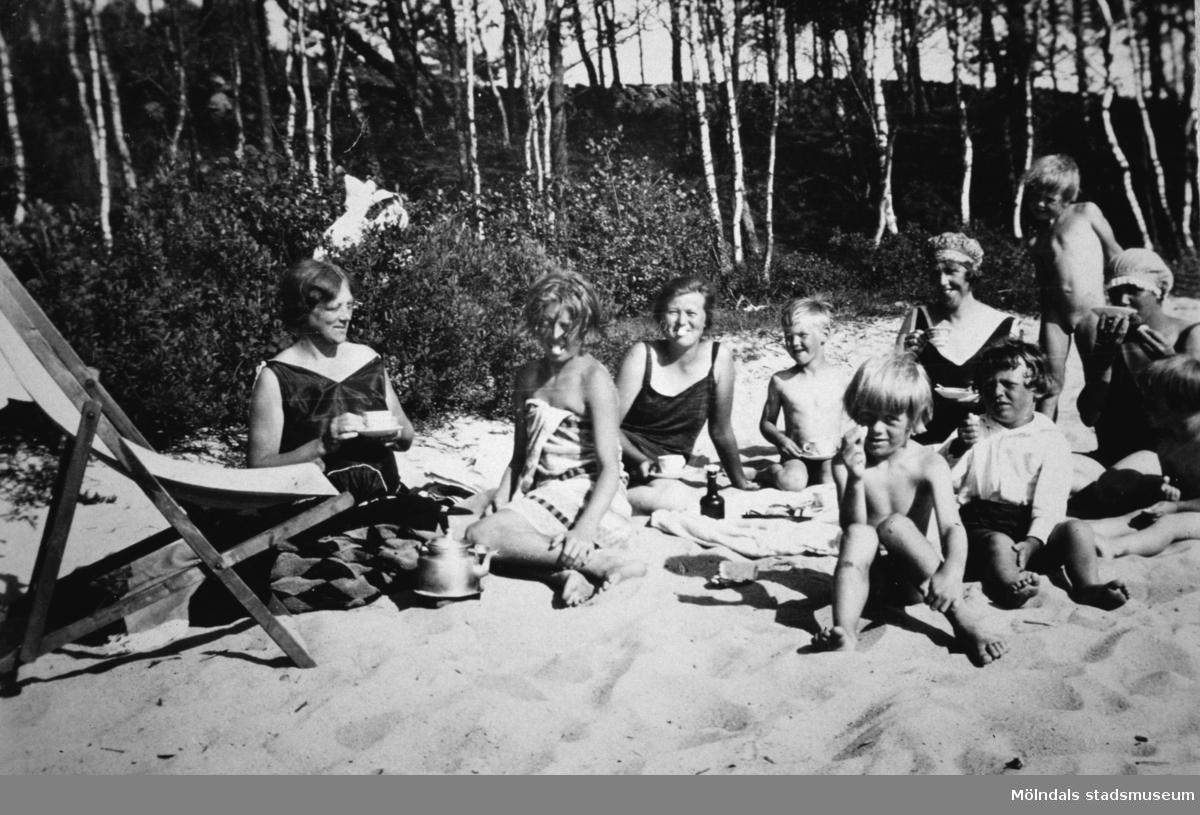 Barn och kvinnor sitter på sandstrand.Ev. vid Tulebosjön.
