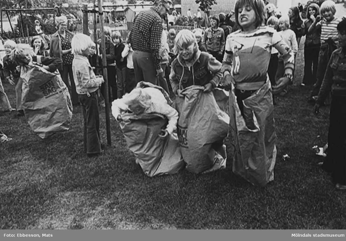 Barn som tävlar i att hoppa säck, 1974 eller 1975.