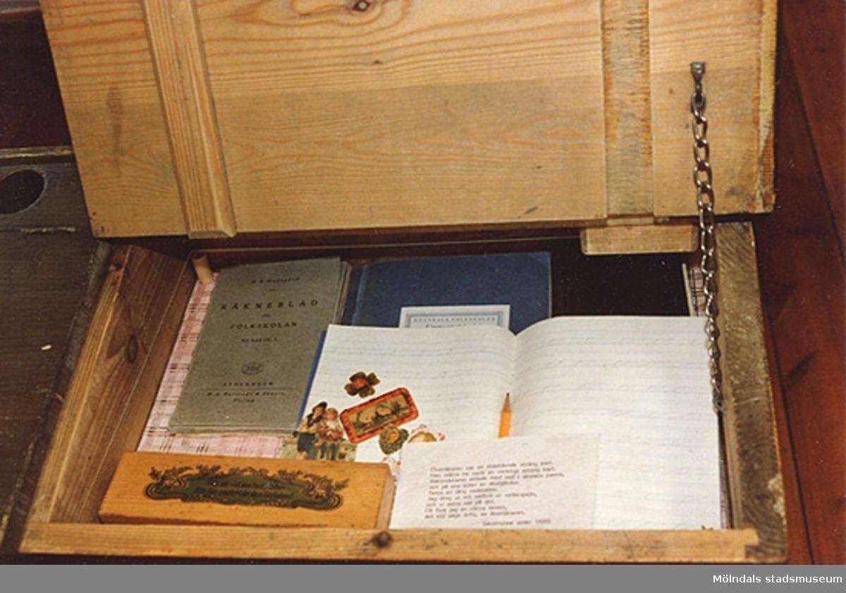"""Utställningen """"Lära för livet"""" 12 mars 1988 - 19 mars 1989 på Mölndals museum.En öppnad skolbänk med typiska attiraljer i."""