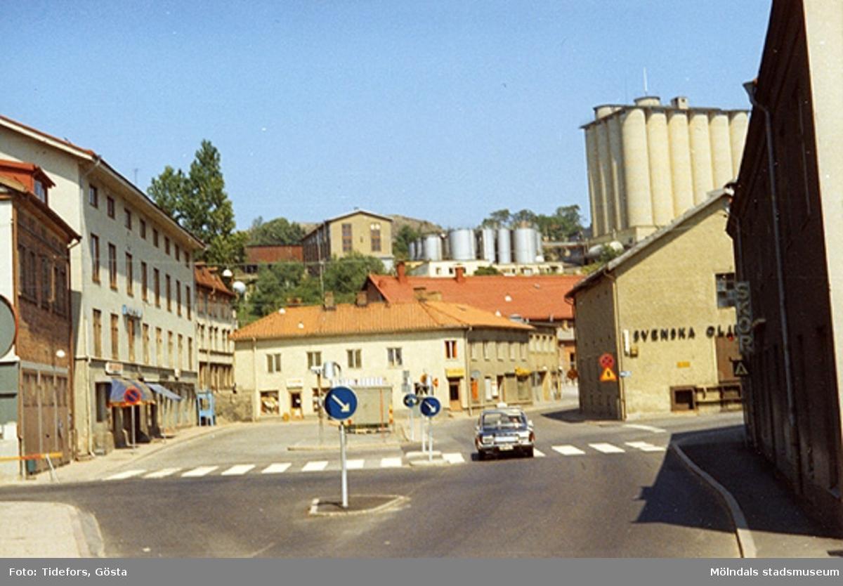 """Det skuggade huset till höger, med skylten """"Skor"""", är Papyrus """"Byggnad 213"""" på Kvarnbygatan 4. Efter detta ses Svenska Oljeslageriet och dess syratorn på höjden."""