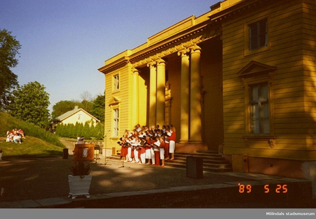 En kör som står framför slottet och sjunger för en liten grupp människor. Kören är klädda i vita och röda kläder.