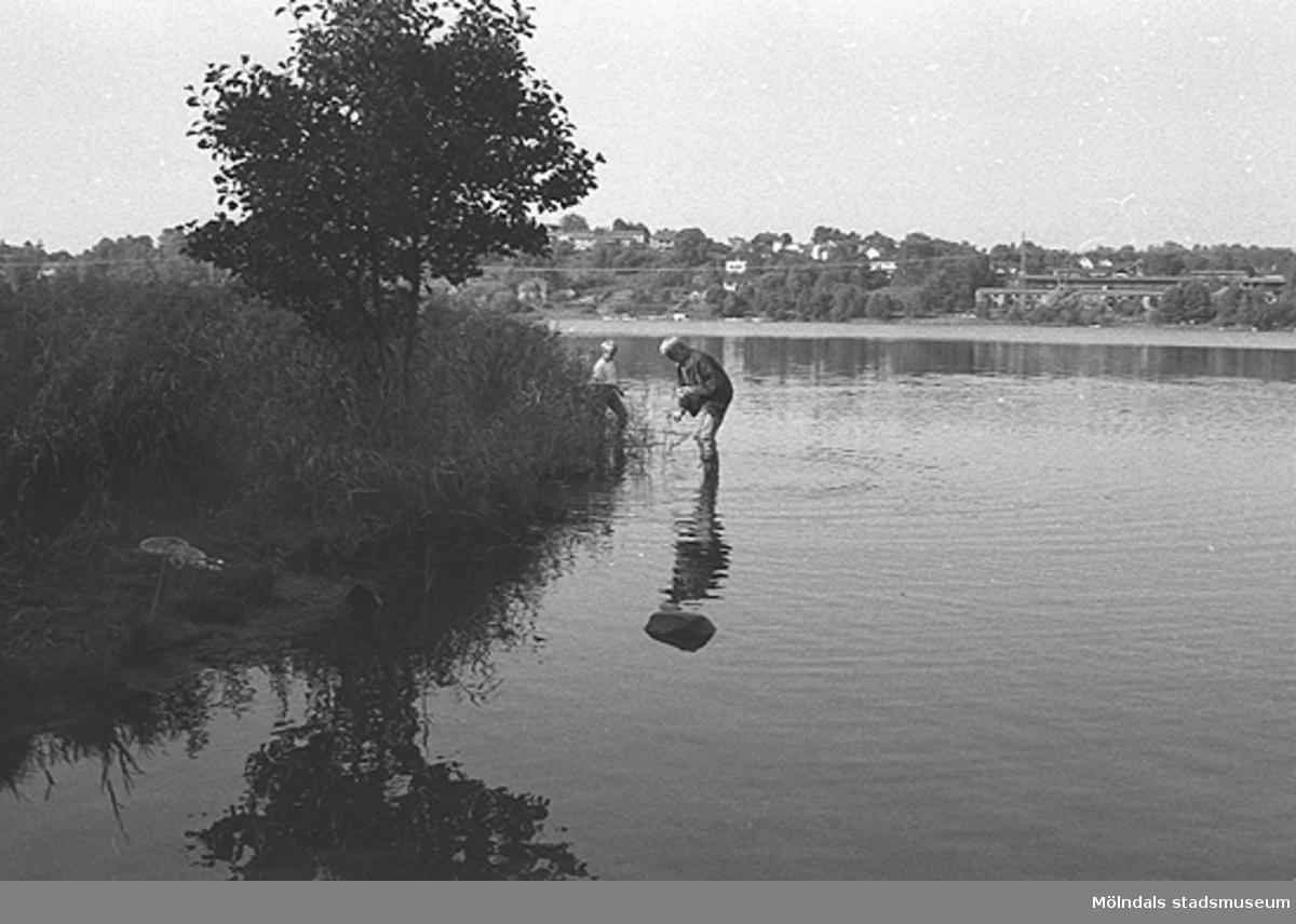 Två personer står i en sjö. Barn på utflykt. Okänd plats och årtal.