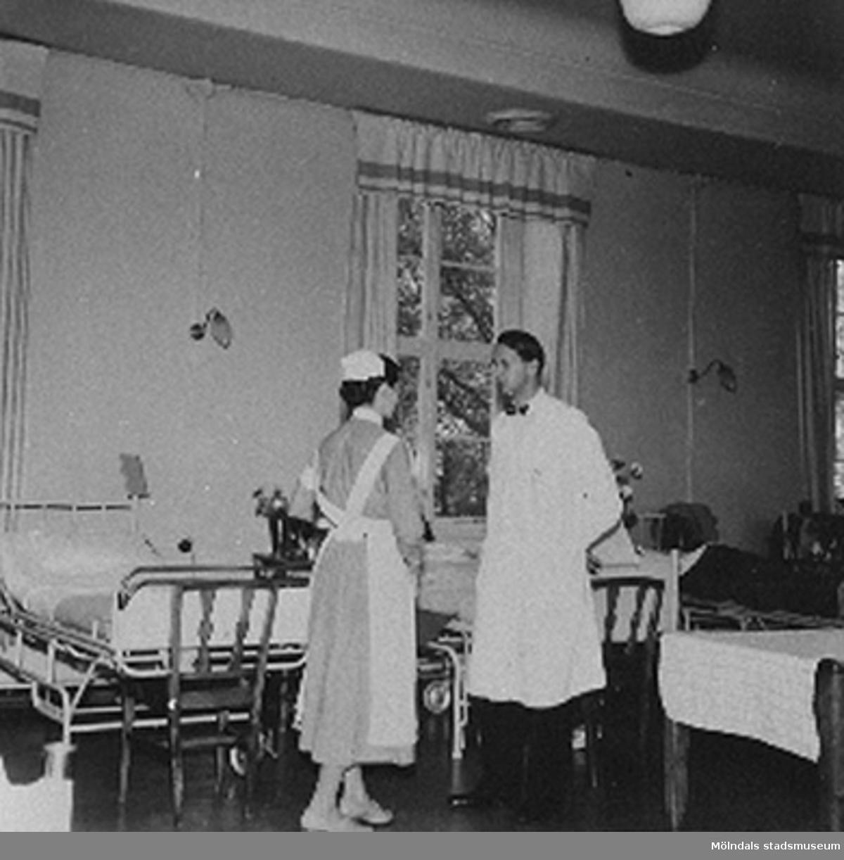 """Avd. läkaren Dr. Bjorwill och ass. sköterskan går på rond på Sabbatsbergs sjukhus i Stockholm, cirka 1958. Det låg 20st patienter i varje sal, 10st på var sida.Vid 18 års ålder fick man börja på Svenska Röda Korsets sjuksköterskeutbildning. Då blev eleven antagen till 3 månaders provtjänstgöring den s.k """"plättperioden"""". Under denna tid användes en liten mössa till arbetsuniformen som man fick vid utbildningens början. Den lilla mössan avvek från den ordinarie mössan för att visa att eleven gick på prov. Efter provtjänstgöringen fick eleven veta om hon godkändes för vidare utbildning på 3,5år. Efter 2 års studier fick eleven bära den vita armbindeln och blev därmed undersköterska.Arbetsuniformen var skräddarsydd och bestod av en blå bomullsklänning, ett vitt förkläde som knäpptes i kors i linningen med särskilda manschettknappar och en vit mössa. Klänningens längd skulle vara ett visst antal centimeter ovanför golvet och förklädet skulle vara ett visst antal centrimeter ovanför den nedersta klänningsfållen. Man fick endast använda svarta strumpor och svarta skor eller bruna strumpor och bruna skor till klänningen.Till klänningen hörde också en vit krage till som fastsattes med knapp baktill och  med sjuksköterskebroschen framtill. Till klänningen fanns ett särskilt bälte som gjorde att förklädet inte skulle vika sig i midjan. På vänster ärm fastsattes den vita armbindeln som visade att det var en Röda Kors syster! Den vita mössan var enligt ett mönster särskilt för Röda Korsets sjuksköterskor (varje sjuksköterskeskola hade sin egna design av mössan). Endast nålar med pärlhuvud fick användas på mössan. På mössan fästes hakrosetten. Vid utomhusvistelse fick man bära den tillhörande svarta kappan. Den skulle vara längre än klänningen. Till kappan var man tvungen att använda svarta strumpor och svarta skor och sätta fast den vita armbindeln på vänster ärm. Man använde också en särskild mössa med hakband den s.k Kapotten. Det fanns också en tillhörande frack till uniforme"""