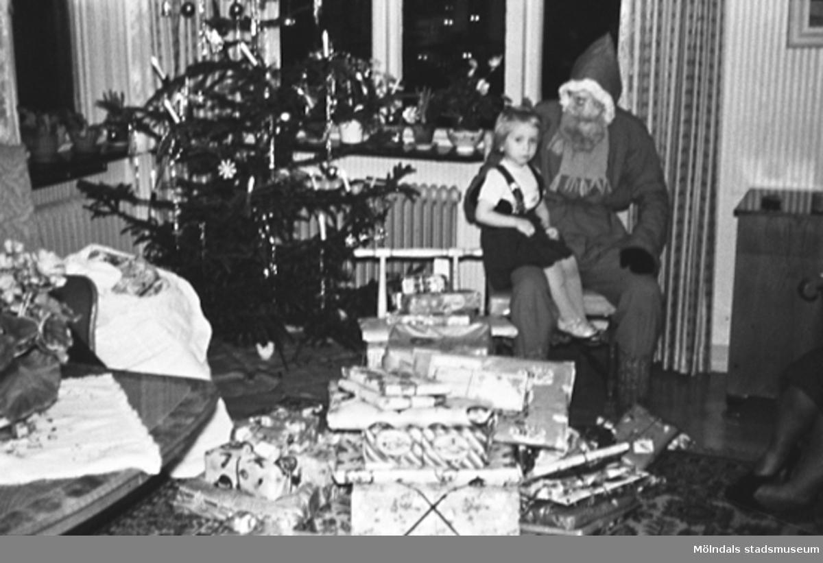 Jultomte med en flicka i knät och julklappar framför sig.