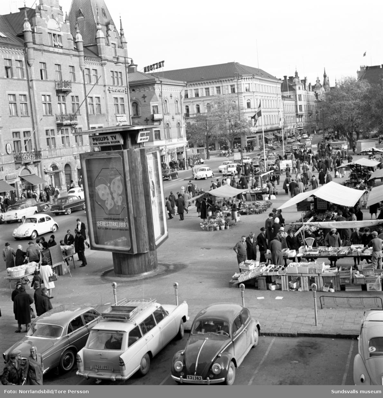 Lördagsrusning i city. Människor och bilar trängs på Storgatan och torget. Vänstertrafik.