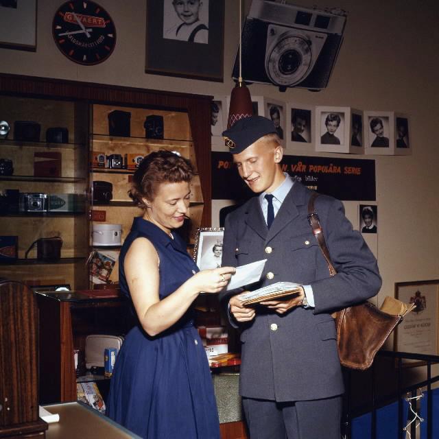Brevbärare iklädd postens uniform från 1962 års beklädnadsreglemente, överlämnar post till kvinnlig expedit i en fotobutik. Brevbäraren på bilden är med stor sannolikhet Owe Jonsson. Owe Jonsson var brevbärare i Växjö och vann EM-guld i Belgrad den 16 september 1962 i löpning 200 meter, bara 13 dagar senare omkom han i en bilolycka.