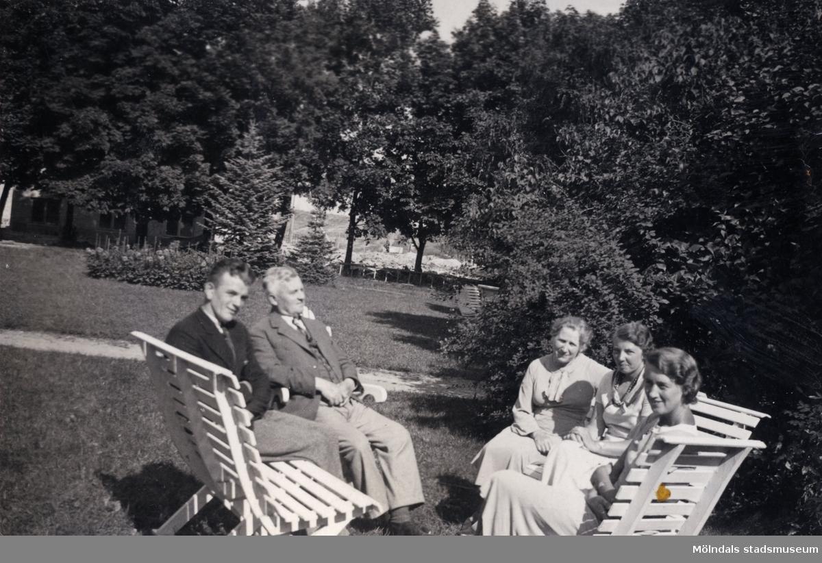 """Kvinnor och män fotograferade sittandes i trädgården, Stretered i Kållered. """"Ur Ivars fotoalbum."""""""