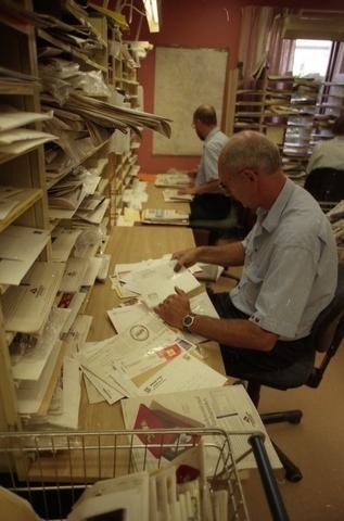 Lantbrevbärare Reinhold Andersson med flera posttjänstemän, sorterar post inne i sorteringsdelen på en postanstalt. Tillhör en dokumentation av en lantbrevbärare i trakten av Valdermarsvik av fotograf Ove Kaneberg.