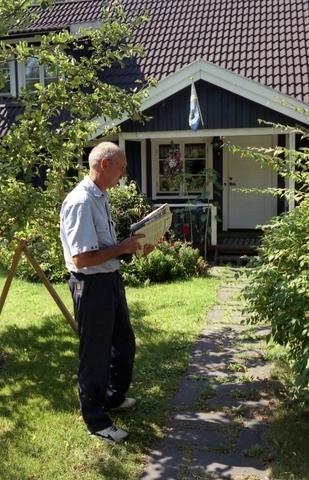 Lantbrevbärare Reinhold Andersson delar ut post under sin lantbrevbäringstur. Tillhör en dokumentation av en lantbrevbärare i trakten av Valdermarsvik av fotograf Ove Kaneberg.