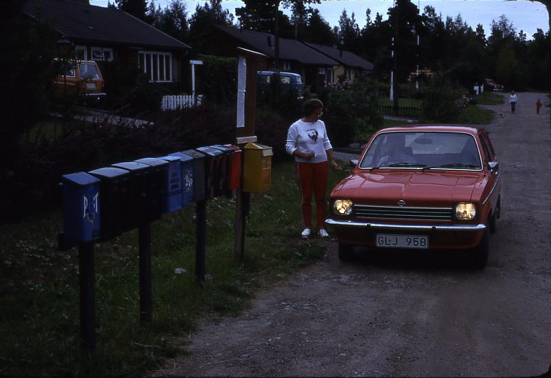 Lantbrevbärare Mikael Mattsson har kommit till Rocksta. Gunvor Wessberg står vid bilen och samtalar med honom. I förgrunden syns en samling postlådor och en gul brevlåda.