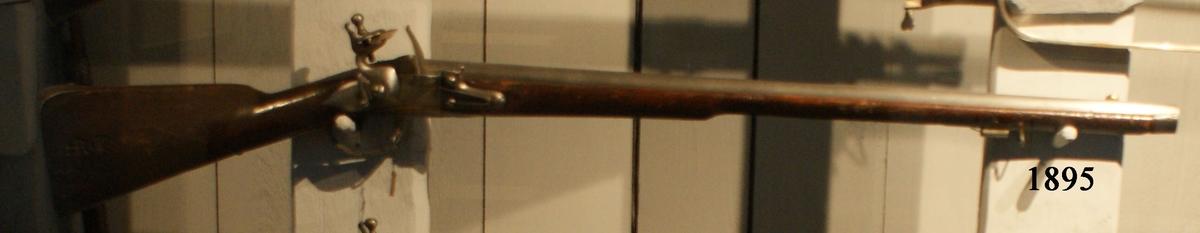"""Musköt, 1725 års modell. Flintlås, slätborrad, utan bajonett. Märkt: """"I.F. 93"""". Kolven av trä, pipa och mekanism av stål. Beslagen av metall. Pipan troligen en avkortad m/1725 (se Nr 1853). Pipanslängd 800 mm."""