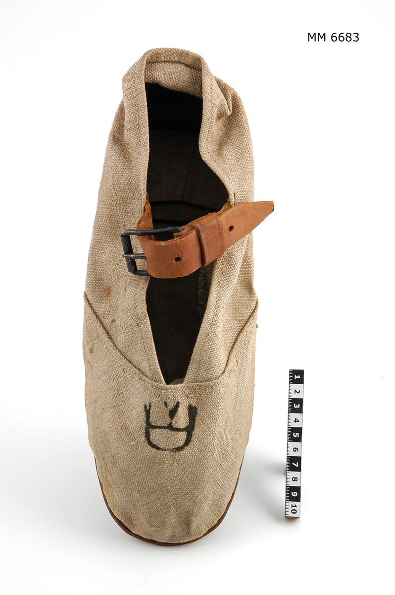 Sko av segelduk med sula och bakkappa av läder. Över vristen försedd med rem med sölja. Kronstämplad.