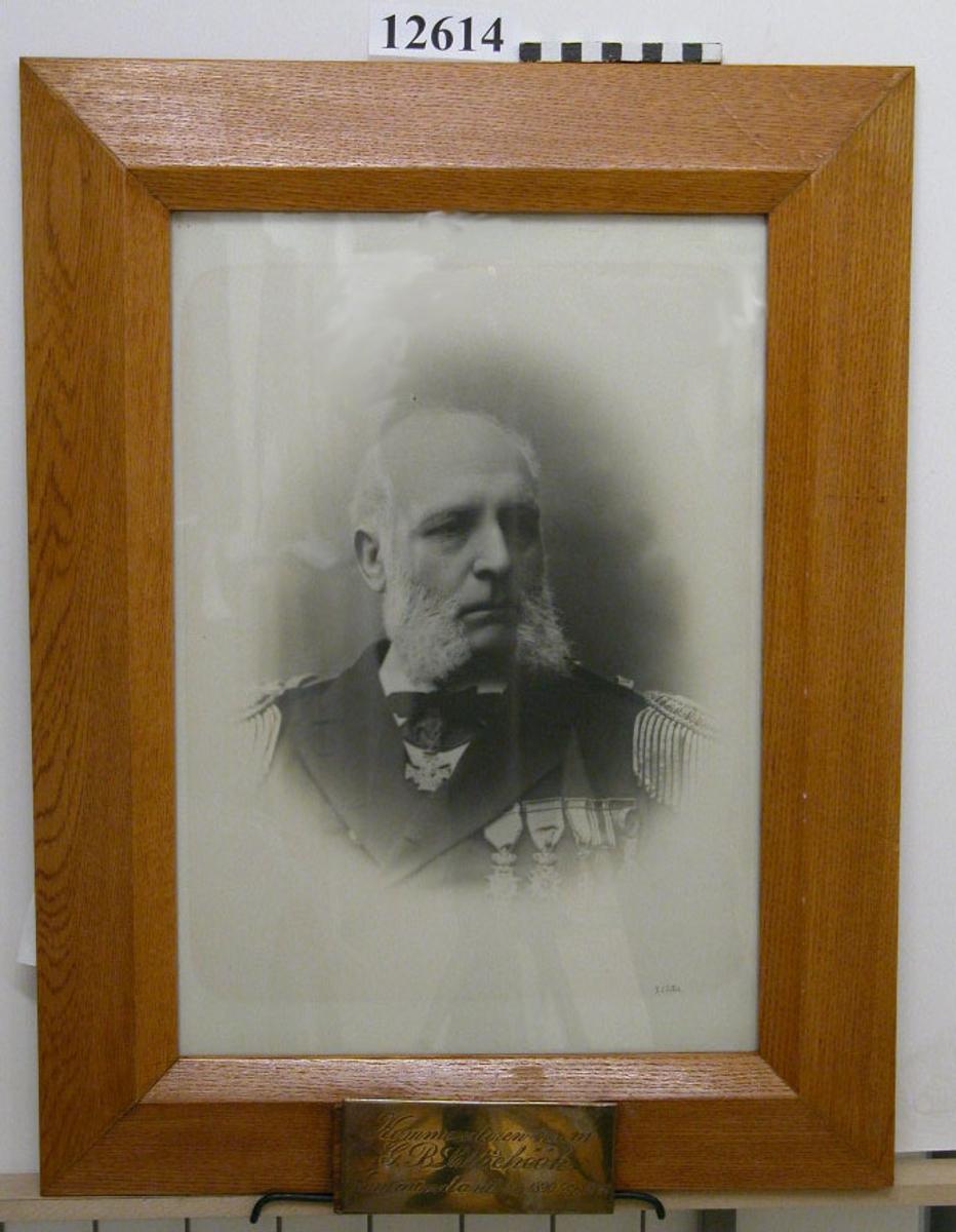 Personfotografi inom glas och ram av ek. Text på namnplåt av försilvrad mässing: Kommendören  m.m. G. B. Lilliehök Kommendant 1/10 1890-30/9 1893. Neg.nr 4936-4947