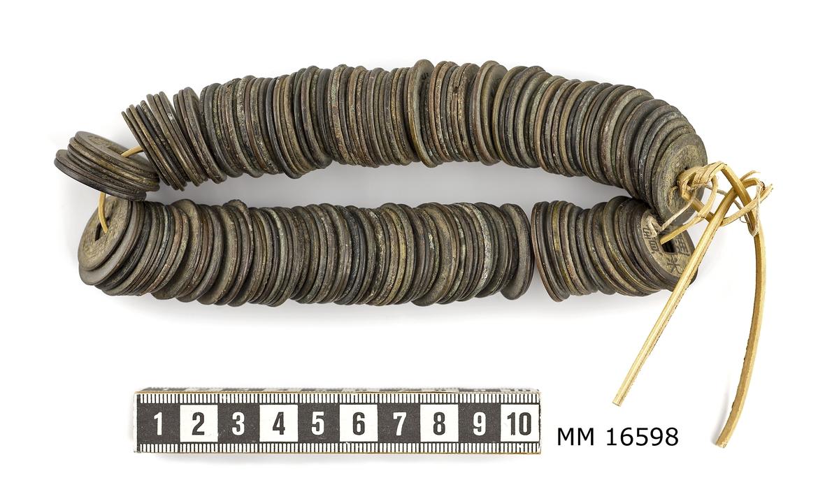 Mynt, kinesiska, chienmynt (eller cashmynt). Bambusnöre med uppträdda mynt av brons. Mynten är olika stora och olika välbevarade.