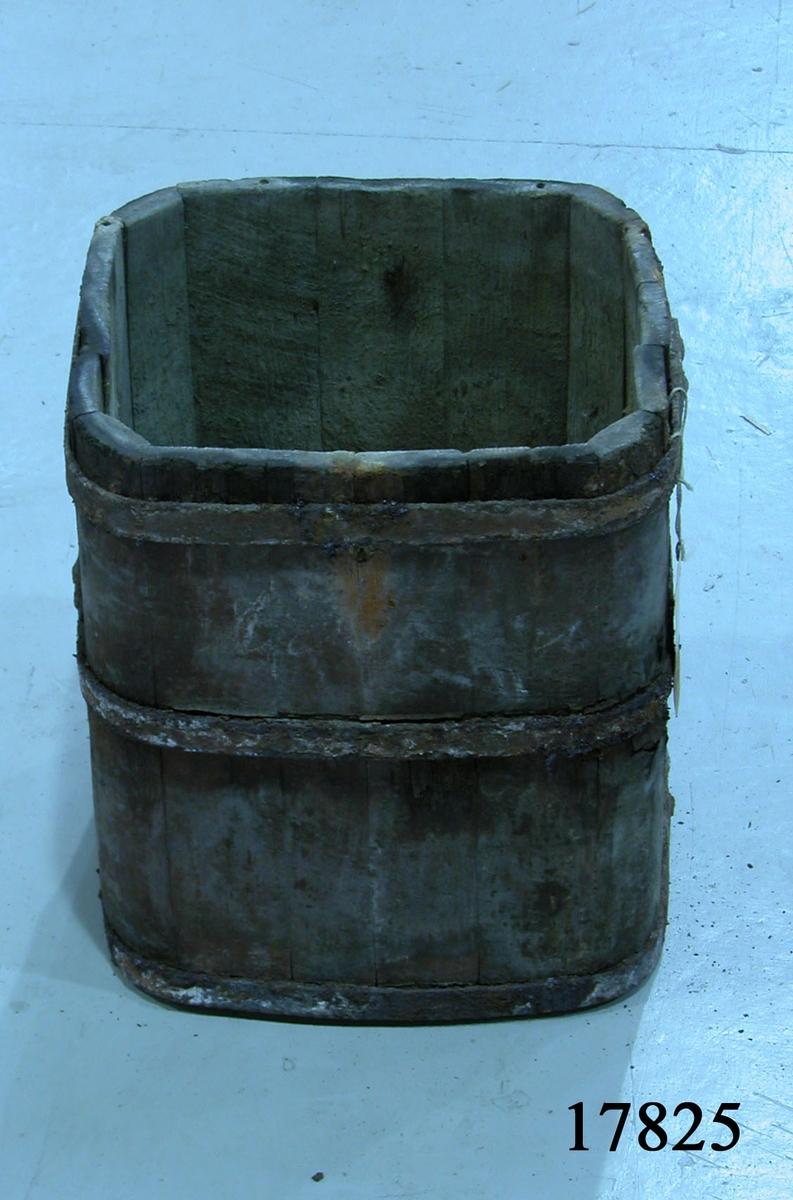Tunna av fur,, rektangulär form med rundade hörn. Järnband nitat kring botten samt två band runt tunnan. Spår av två handtag på kortsidorna.