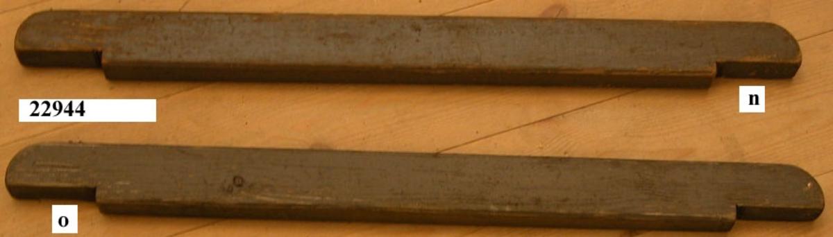 Fotstöd som i vardera ändan har urfasningar för att passa i stöd som är fastsatta på durktrallarna i livbåten. Det första av två likadana fotstöd.