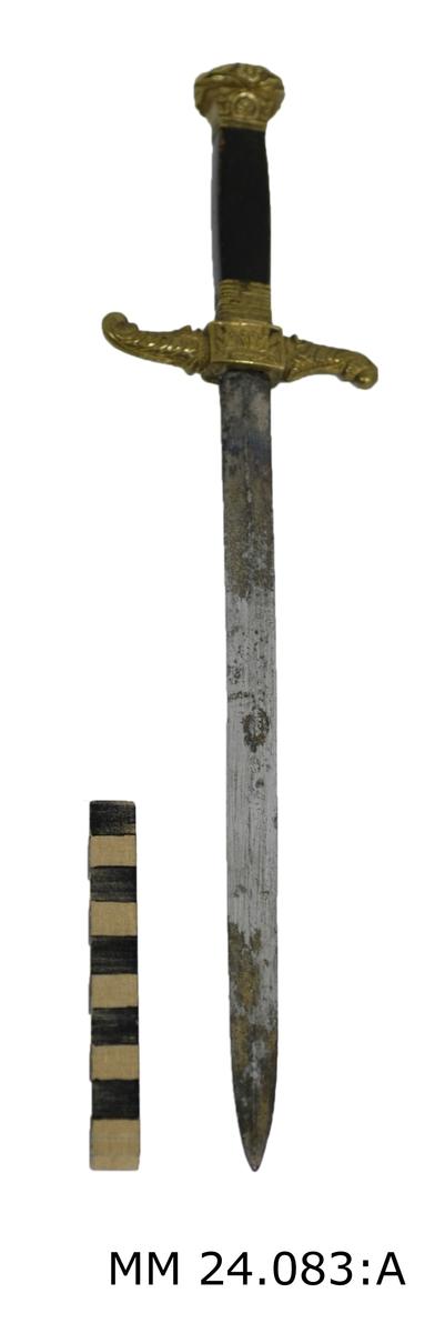 Tveeggad klinga med rygg på var flatsida. Fäste av mässing. Ornamenterad knapp av mässing. Ornamenterade parerstängsarmar, den ena uppåtsvängd den andra nedåtsvängd. Svartmålad kavel av trä.