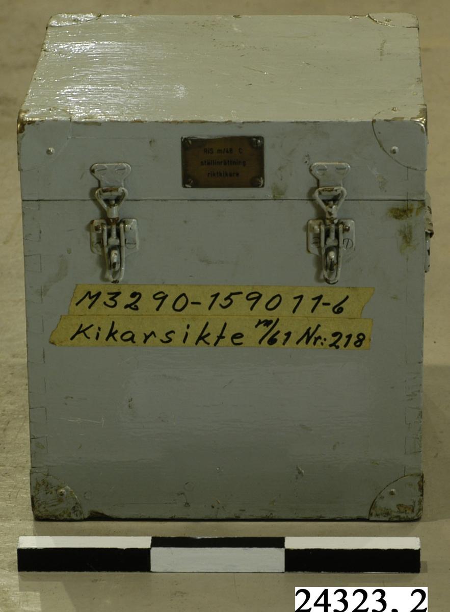 """Gråmålad låda av trä. Försedd med två haspar på framsidan, handtag på sidorna och en mässingsbricka på framsidan försedd med texten """"RIS m/48 C, ställinrättning, riktkikare"""". I lådan finns ett fack innehållande glödlampor i reserv. På lådans framsida sitter en tejpremsa försedd med texten """"M3290-159011-6, Kikarsikte m/61 Nr: 218. Metallskodda hörn."""