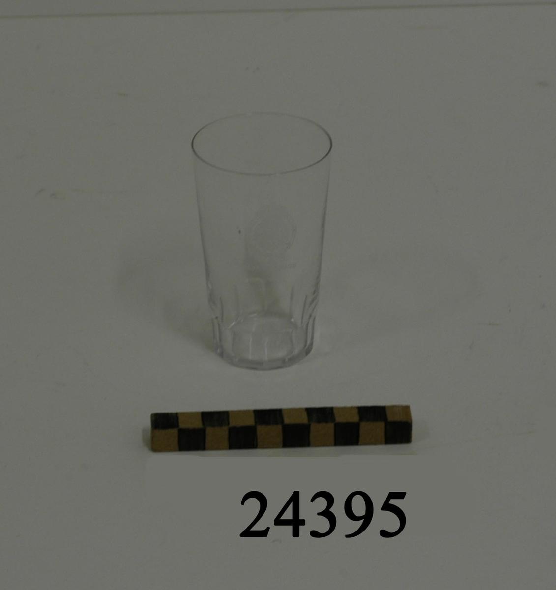 """Selterglas, cylinderformat, tunn botten, utan fot, något större i mynningen än botten. Bågformad slipning i glasets nedre kant. På glasets mitt graverad dekor: lilla riksvapnet omgivet av koldinerorden därunder: """" H.M.S. SVERIGE """" Diameeter: 55 mm mynning,  D = 40 mm botten"""