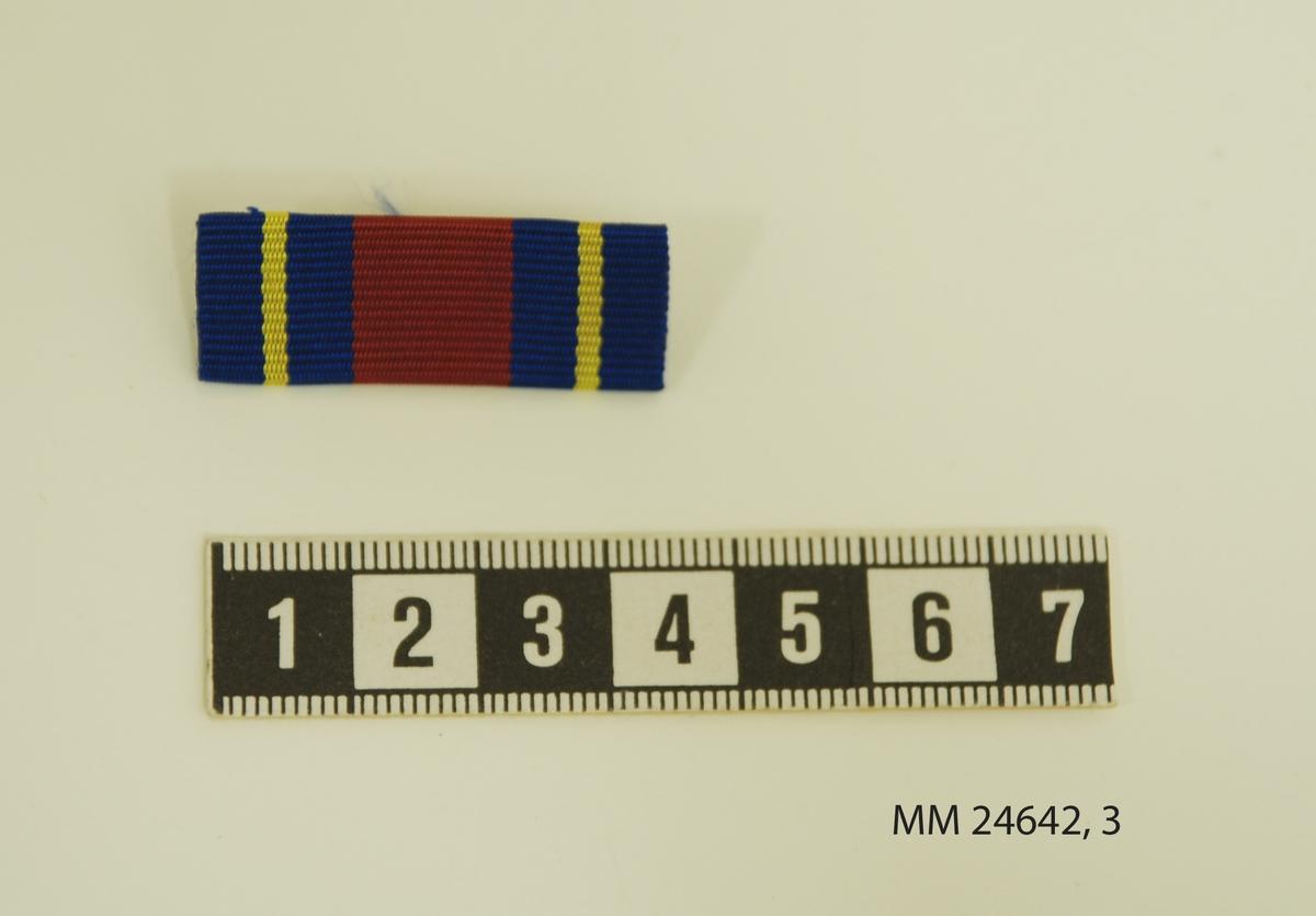 Släpspänne, förtjänstband av räfflat sidenband på rektangulär bricka. Randning i färgerna rött, blått och gult. Fästnål på baksidan.