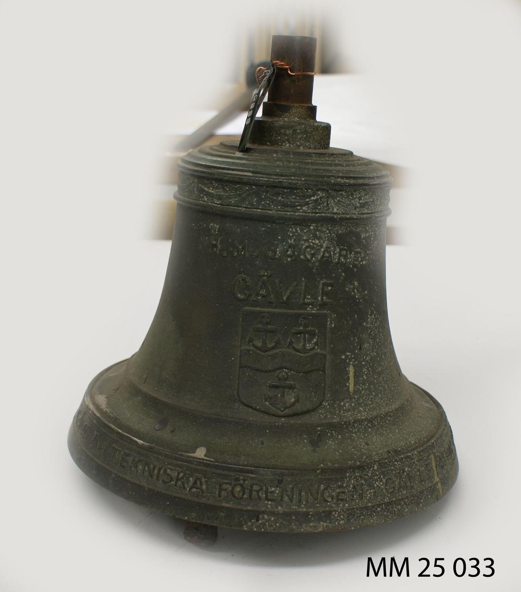 """Skeppsklocka av brons märkt i relief: """"HM Jagare Gävle"""" samt Gävles stadsvapen, motiv av tre ankare. Märkning på klockans mynning: """"Gåva av tekniska föreningen i Gävle april 1941"""". Kläpp av järn. Lapp med märkning: """"SSS 323""""."""
