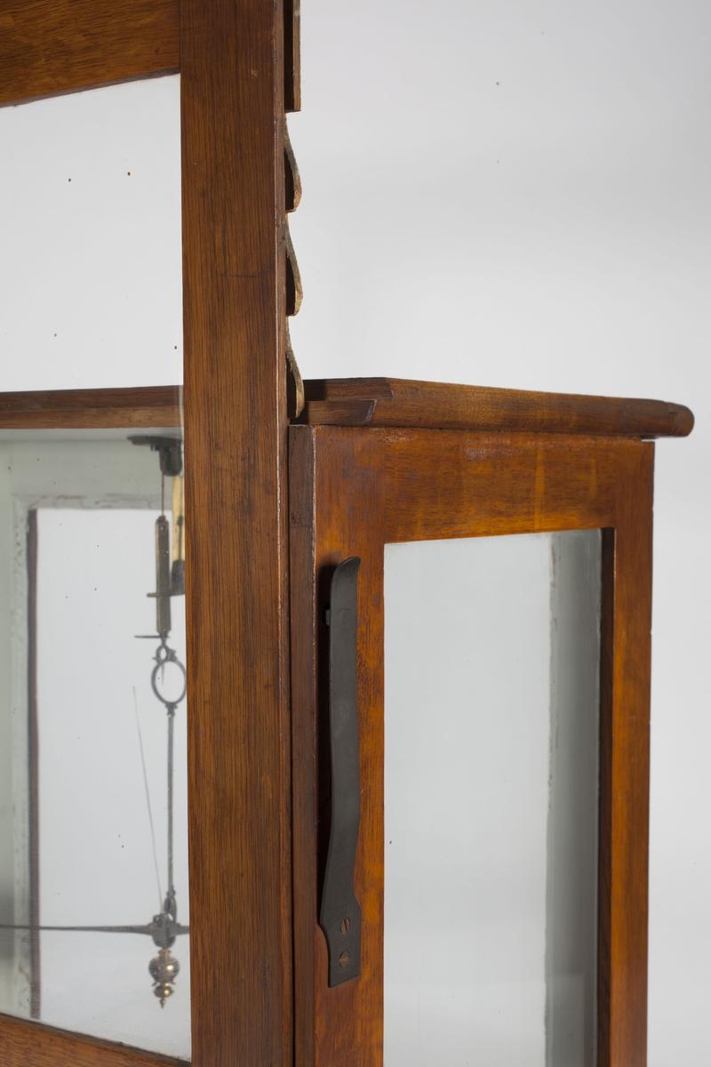 """Vekten er bygd inn i en rektangulær kasse med glassvegger. Det er en snor til å henge opp vekta med, to vektskåler og to løse """"kopper"""" som hviler i disse. De to langveggene kan heves trinnvis. Under vekthuset er en skuff, trolig til å ha loddsatser i. Hele vekta står på tre stillbare bein. Innvendig er karmene rundt glasset malt hvite."""