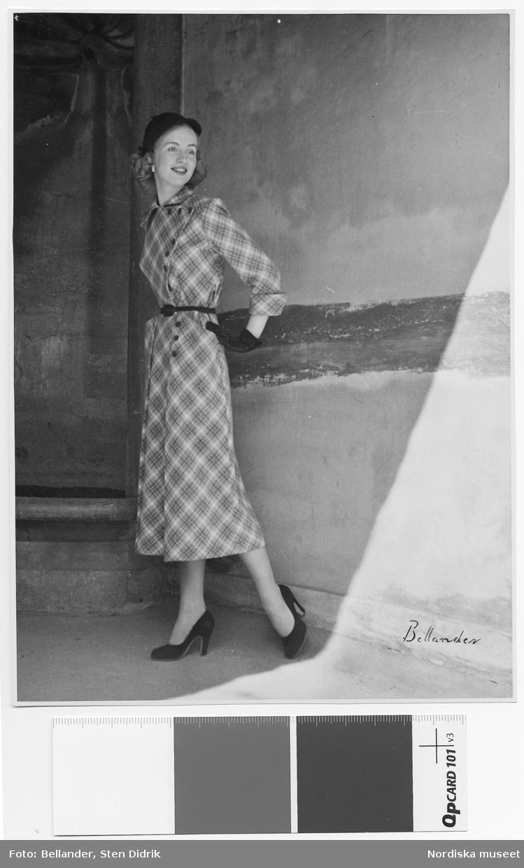 Modell i rutig klänning med smalt skärp, hatt och handskar, framför stenvägg.