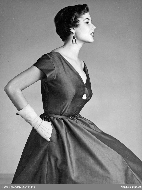 Modell i v-ringad klänning, handskar och trekantiga örhängen.