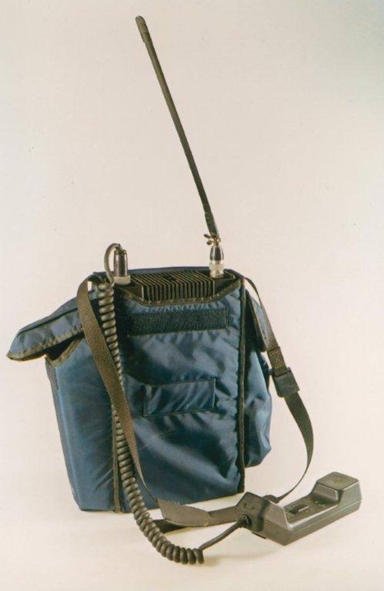 Form: Rektangulær kassett med håndtelefon og antenne. Bæreveske.