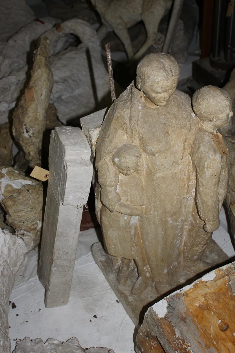 Skulptur i gips av en kvinne med to barn foran et kors. Til monument over falne 1940-1945 i Larvik, 1:3. Orginalen er hugget i stein.