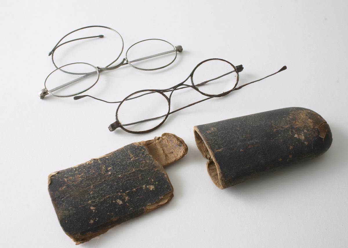 To par briller i et brillehus. Brillene er laget av metall og glass. Små ovale brilleglass, med innfatning. Det ene paret sannsynligvis av sølf - det andre av stål (med mye rust). Brillehuset består av to deler til å sette sammen laget av brun papp. Sølvbriller: L: med glass: 11,5 cm, L: Stang: 16,5 cm, Stål-briller: 11 cm; L: Stang: 12,5 cm, Brillehus L: 17 cm, B: 5 cm
