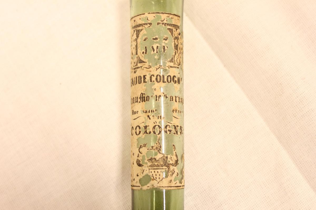 """En lang smal flaske i grønt glass. Uten kork. Det som kan tydes av tekst er:"""" J M E? eller F?  Eaude cologne. Cologne"""""""