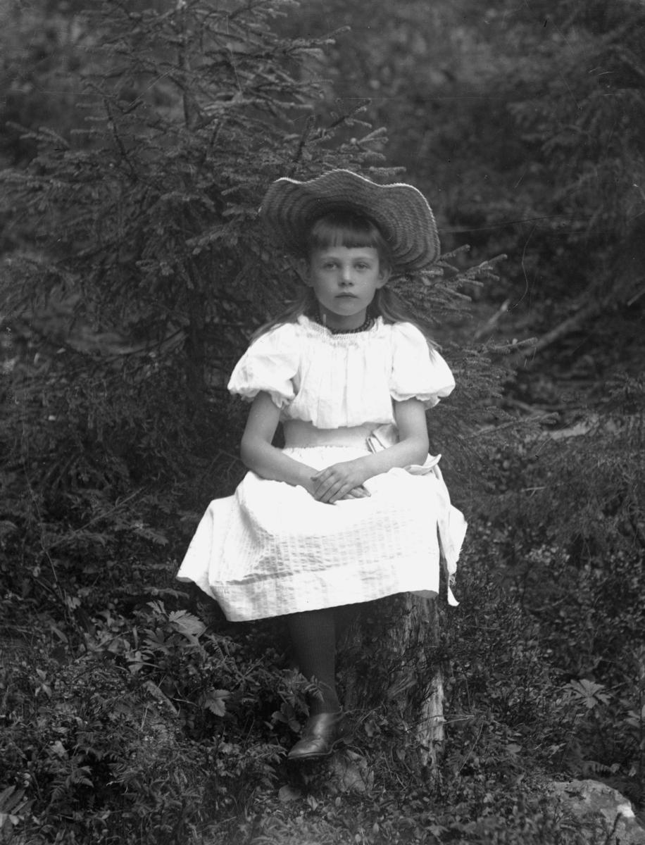 Jente i hvit kjole og hatt, sittende i skog