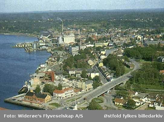 Oversiktsbilde og flyfoto over Sundbryggene og  Moss sentrum i 1964. Bildet viser tydelig  omfanget av bygninger som måtte rives for å realisere Rådhusbrua tidlig på 1960-tallet.