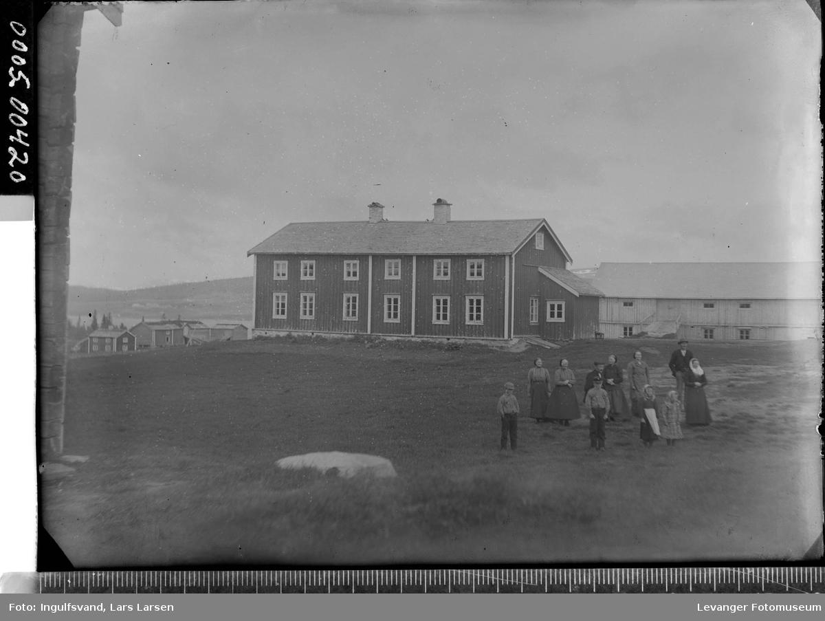 En gruppe mennesker foran et våningshus og låve.