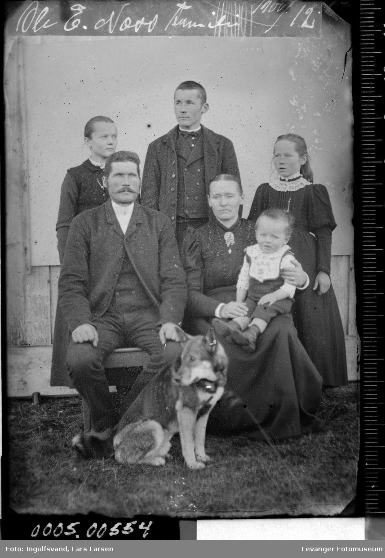 Gruppebilde av to menn, to kvinner, to barn og en hund.
