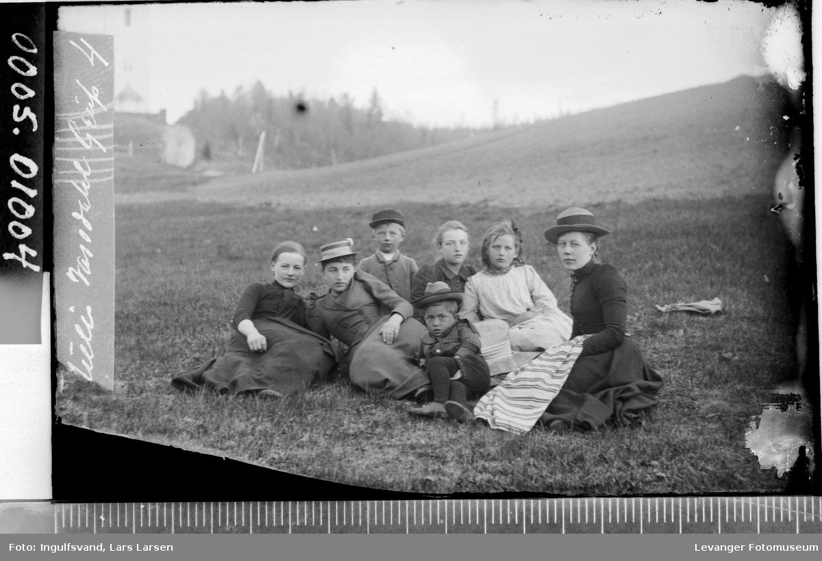 Gruppebilde av fem ungdommer og to barn sittende på bakken.
