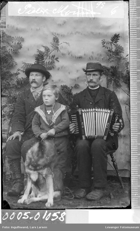 Gruppebilde av to menn, en gutt og en hund.